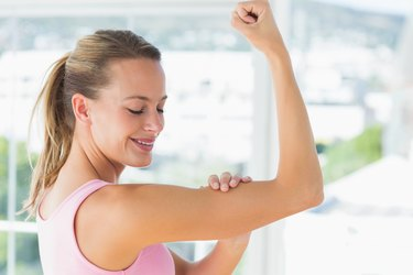 Young woman flexing muscles in the gym