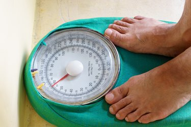 Man's feet standing on a weighing scale
