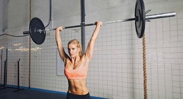 Muscular young woman doing weightlifting at gym gym. Fit female model lifting heavy weights at gym.