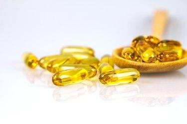 Closeup yellow soft gelatin supplement fish oil capsule