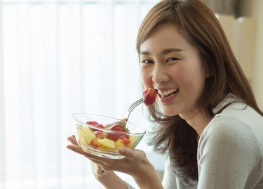 Asian woman is happily eating her fruit salad