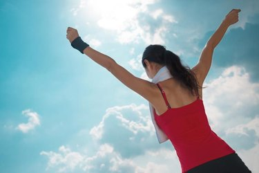 Active woman with outstretched arms against the blue sky, rear view
