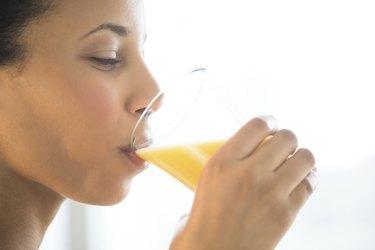 Close-Up Of Woman Drinking Orange Juice