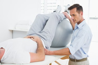 Physical therapist assisting man with yoga ball