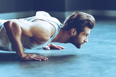 Side view of young handsome man in sportswear doing push-up at gym