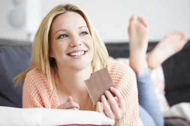 Teenage Girl Eating Bar Of Chocolate At Home