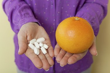 Woman hand with pills medicine tablets and grapefruit