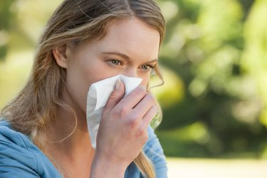 Woman blowing nose with tissue paper at park