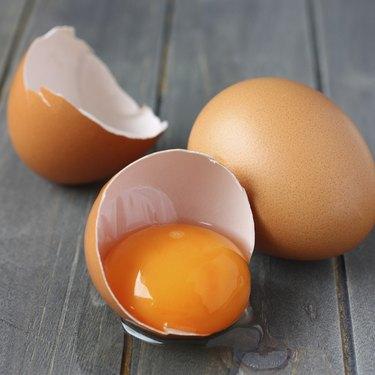 Broken fresh egg on rustic wooden background