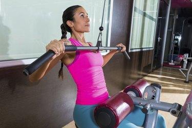 Lat pulldown machine woman workout at gym