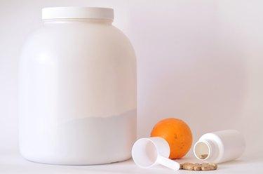 Big jar of protein powder, bottle of pills, orange