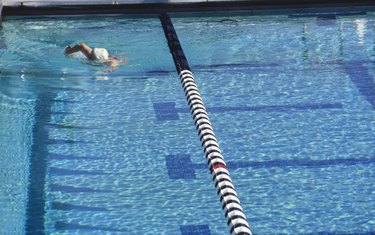 Senior woman swimming in outdoor pool, elevated view