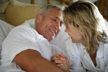 Senior couple smiling in bed, close-up