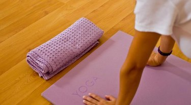 women hands on a ''YOGA'' printed yoga mat,on a wooden floor with towel