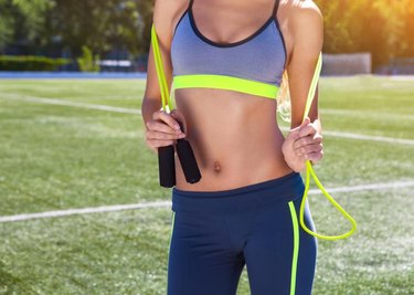 Woman with jumping rope. Beautiful young woman standing with a jumping rope in her hands with a stadium as background