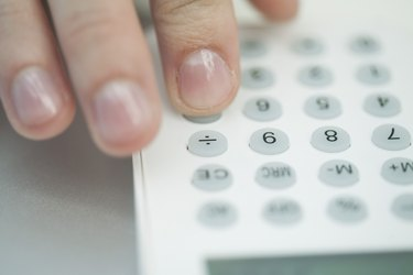 Woman using calculator, extreme close-up