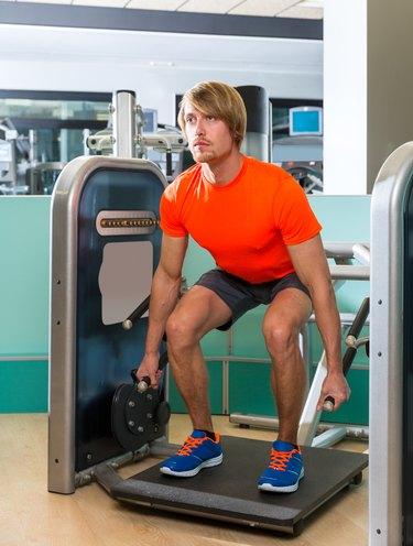 Gym squat machine exercise workout blond man