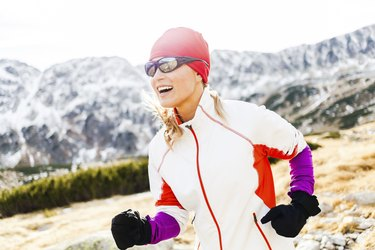 Happy woman running in mountains, sunny day