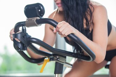 Beautiful woman at the gym on bike, cycle
