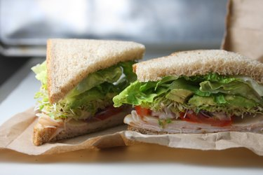 Healthy turkey avocado and sprouts sandwich on whole wheat lunch