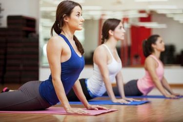 Cute Hispanic women practicing the cobra pose during their yoga class in a gym