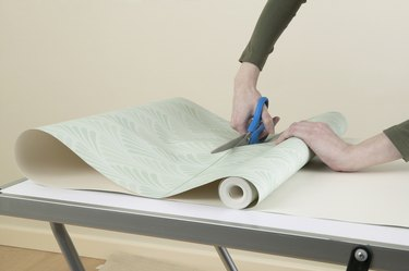 Person cutting through roll of wallpaper