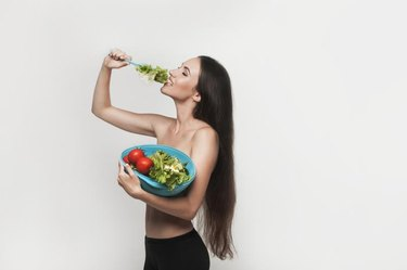 Beautiful young brunette woman with slim body holding bowl with fruits and vegetables. Healthy eating lifestyle and weight loss concept.  White background