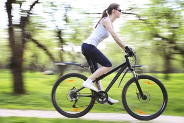 Image of woman riding bicycle in a green park