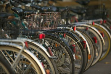 photograph of a row of older style bicycles stacked in bike racks