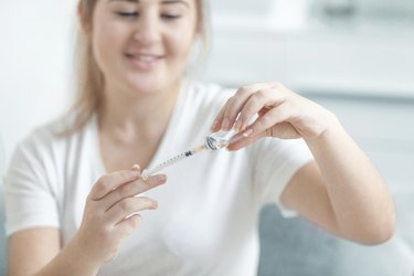 Woman filling insulin syringe with drug