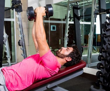 A man with a beard and pink shirt performs inclined dumbbell chest flyes at the gym.