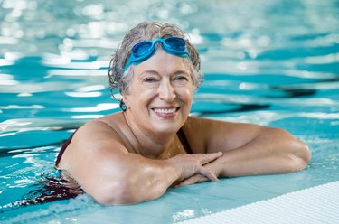 Mature woman wearing swim goggles at swimming pool. Fit active senior woman enjoying retirement standing in swimming pool and looking at camera. Happy senior healthy old woman enjoying active lifestyle.