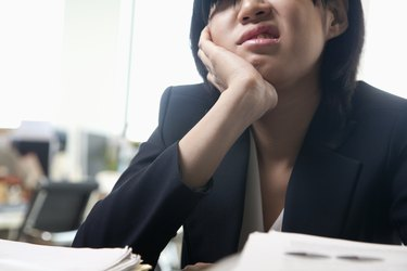 Young businesswoman sitting at desk bored