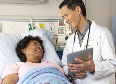 Doctor Using Digital Tablet Talking With Senior Patient