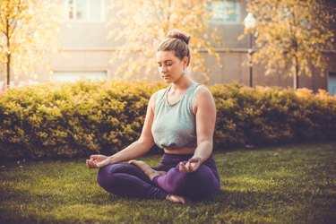 Yoga meditation in lotus pose in park.  Young woman in peace, soul and mind zen balance concept. Toned picture