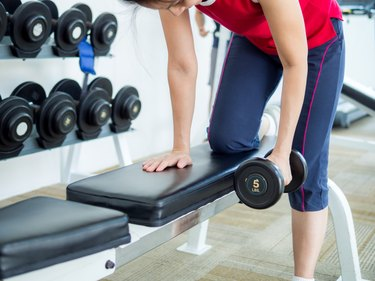Woman exercising with lifting dumbbell in gym
