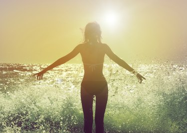Woman facing the sun with waves crashing at her feet