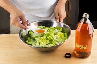 A man dressing salad with ACV to get the benefits of raw unfiltered apple cider vinegar