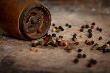 Spice and pepper grinder on wooden background