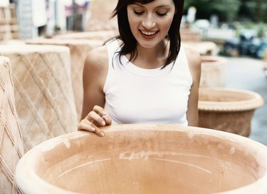 Young Woman Looks at a Large Ceramic Plantpot at a Garden Centre