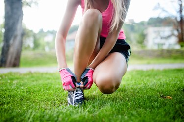 active jogging female runner, preparing shoes for training