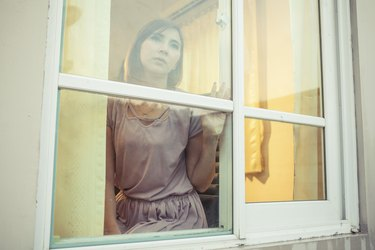Young asian woman is sad at the window