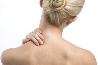 Blond women with neck and backache rubbing area to ease pain