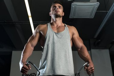 Body Builder Workout On Cable Machine. Standing Low Pulley Deltoid Raise