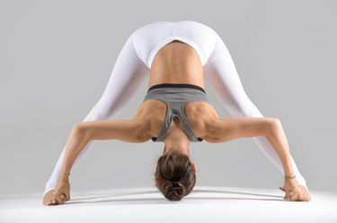 Young attractive woman practicing yoga, standing in Wide Legged Forward Bend exercise, Prasarita Padottanasana pose, working out wearing sportswear, indoor full length, grey studio background