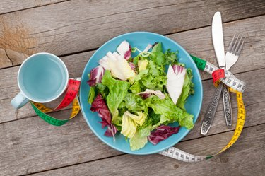 Plate with fresh salad, measure tape, cup, knife and fork