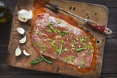 Raw Marinated Flank Steak on an old cutting board