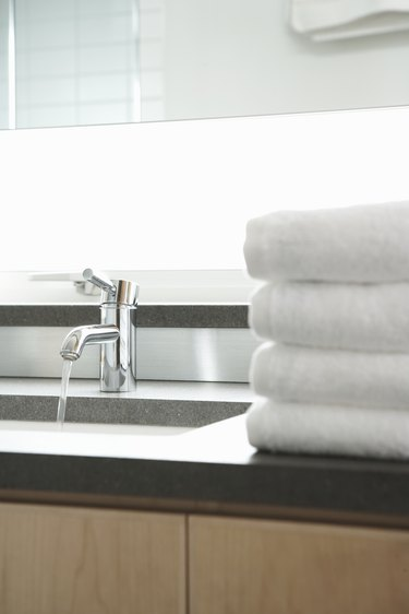 Stack of towels beside sink in bathroom, water running from faucet