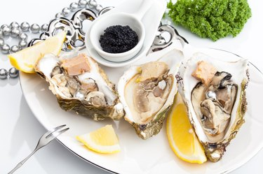 Fresh open oysters on a plate with black caviar