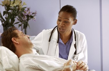 an african american doctor consults with a male caucasian patient as he lies in a hospital bed